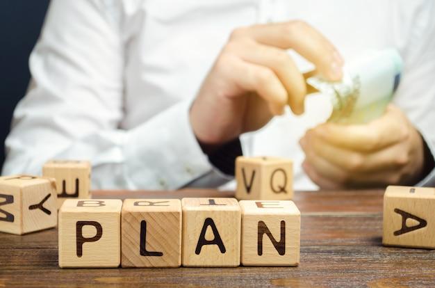 Деревянные блоки со словом план и деньги