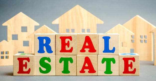 単語の不動産と木造住宅と木製のブロック。