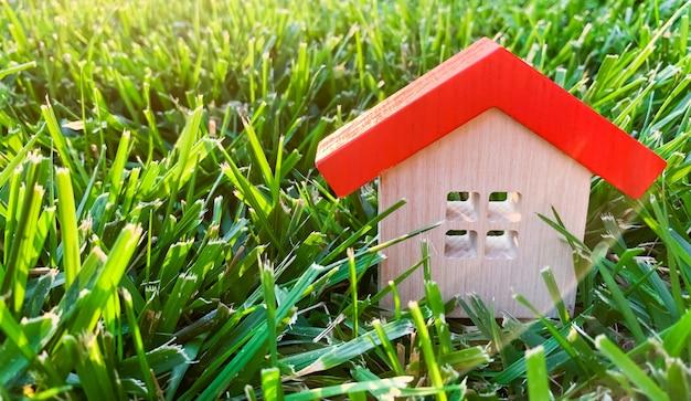 草の上のミニチュア木造住宅。不動産のコンセプト。