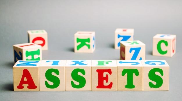 Деревянные блоки со словом активы и случайно разбросанные кубики.
