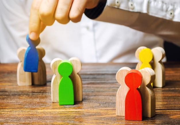 Группы разноцветных деревянных людей и бизнесмен.