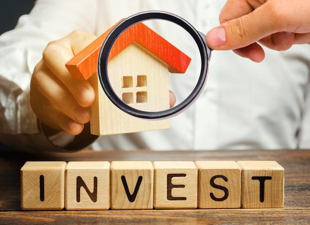 単語投資と木製のブロック、ビジネスマンの手の中に家。