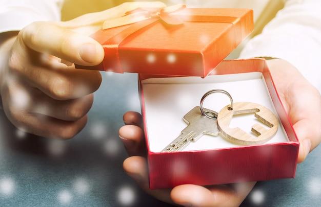 ギフト用の箱と雪のある家の鍵。冬の季節の不動産のための大きい申し出。
