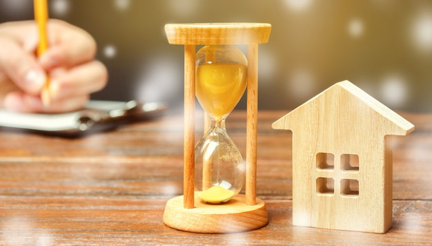 Миниатюрный домик и песочные часы со снегопадом. зимний сезон рынка недвижимости
