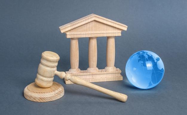Здание суда, молоток и синий шар планеты земля. международный суд. защита интересов бизнеса