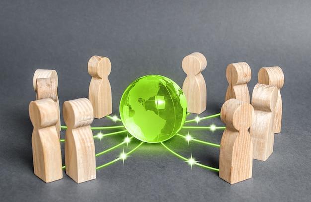Люди окружили зеленый глобус планеты земля. сотрудничество и взаимодействие людей