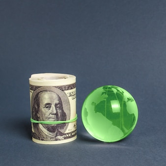 Рулон долларов и зеленая планета земля глобус. международные денежные переводы, привлечение инвестиций