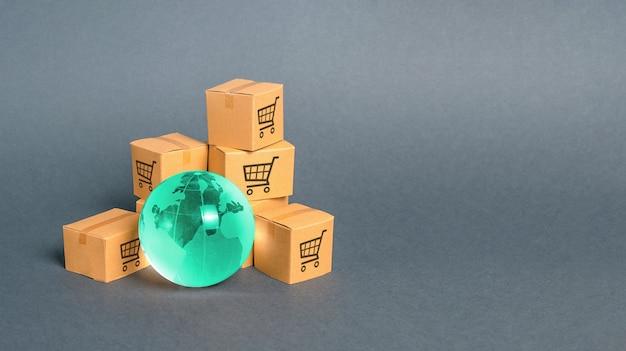Синий стеклянный шар и картонные коробки. распределение и торговля товарами по всему миру