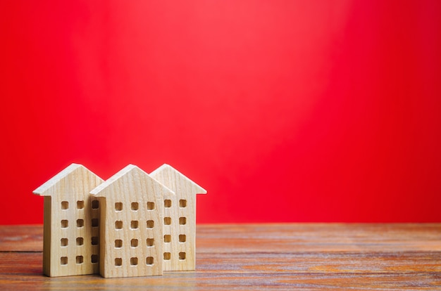 Миниатюрные деревянные дома на красном фоне. концепция недвижимости. город. агломерация