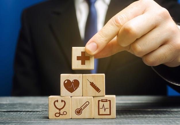 ビジネスマンは、医療シンボルのイメージで木製のブロックを置きます。ヘルスケアと医療