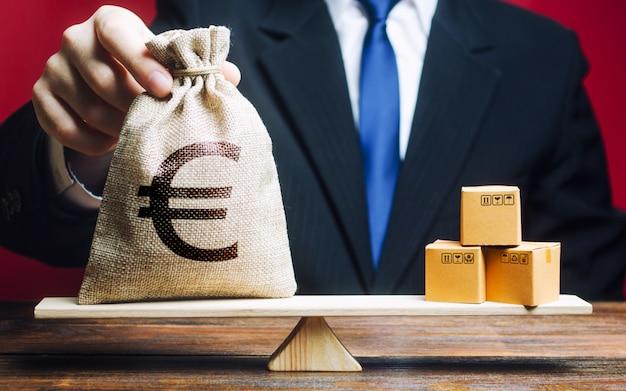 ヨーロッパのユーロユーロシンボルのお金の袋とスケールのボックスの束。貿易収支