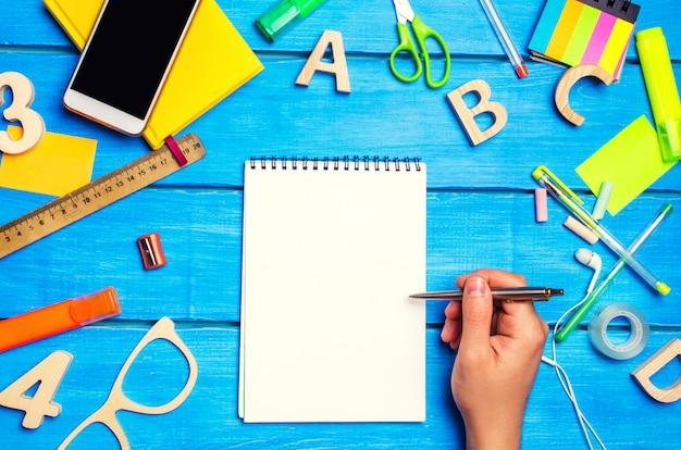 学校のコンセプト、アクセサリー。少年はメモ帳を指しています。新しいアイデア、宿題