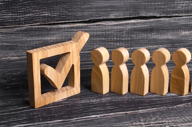 箱の中の目盛りに人々の活気のあるラインが一緒に立っています。選挙の概念