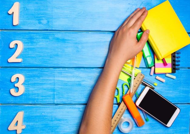Рука школьников очищает прочь школьные принадлежности на синем фоне деревянный стол.