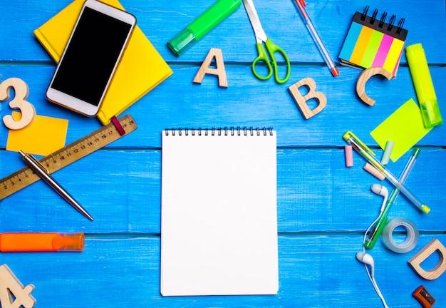 Белая тетрадь на столе ученика среди школьных принадлежностей.