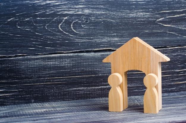 Две деревянные фигуры людей стоят возле входа в деревянный дом.