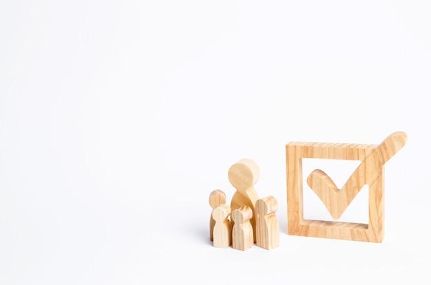 Четыре деревянные человеческие фигуры стоят рядом с галочкой в коробке.
