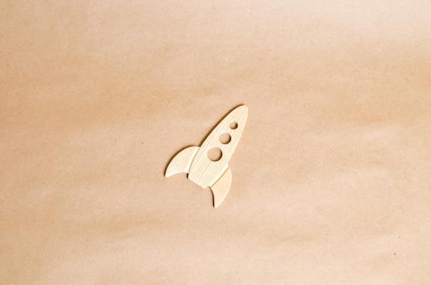 ベージュ色の背景に木製のロケット。
