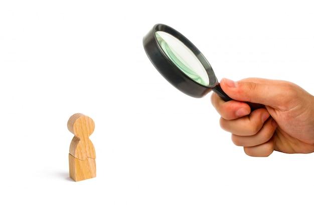 虫眼鏡は白い背景の上の男の木の置物を見ています。