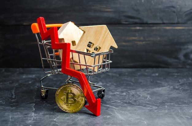 Тележка супермаркета с домами, биткойнами и красной стрелкой вниз. падающая стоимость