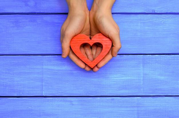 青い木製の背景に手に赤い木の心。