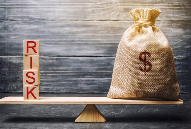 お金の袋と言葉リスクを持つ木製のブロック。金融リスクの概念