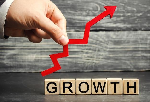 碑文の成長と上向きの矢印。成功するビジネスの概念収入の増加