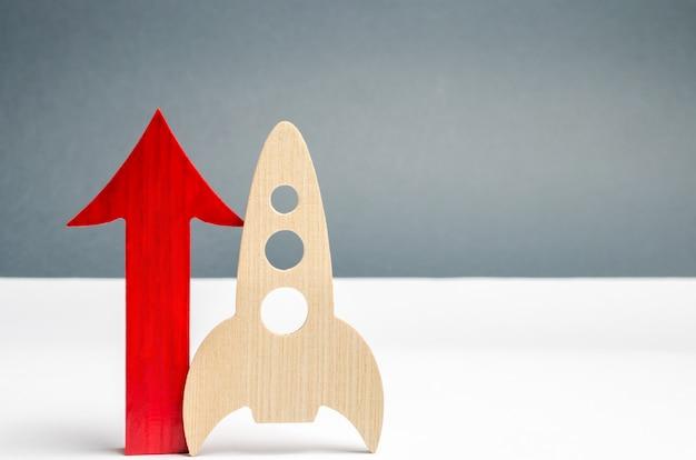 木製のロケットと上向きの矢印。スタートアップの概念スタートアップのための資金を集めるというコンセプト。