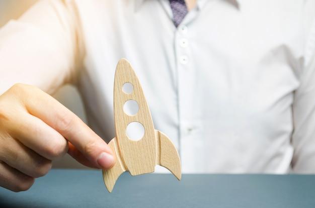 ビジネスマンは彼の手に木製のロケットを保持します。新興企業のための資金調達の概念