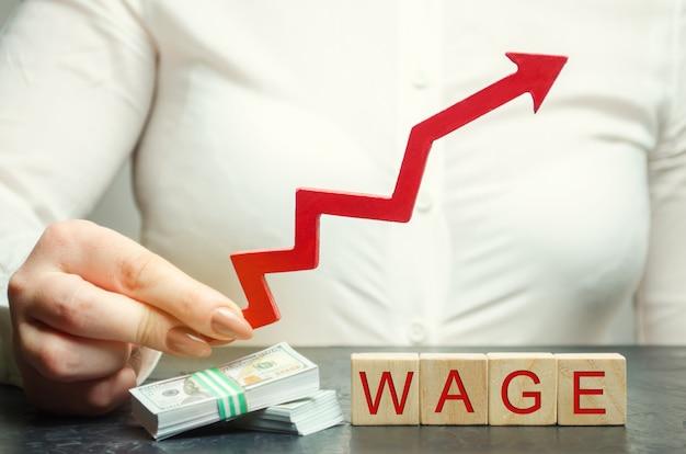 女性の手は単語賃金の上の矢印を保持します。