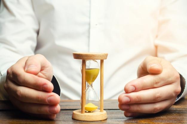 男は砂時計を守ります。時間節約の概念