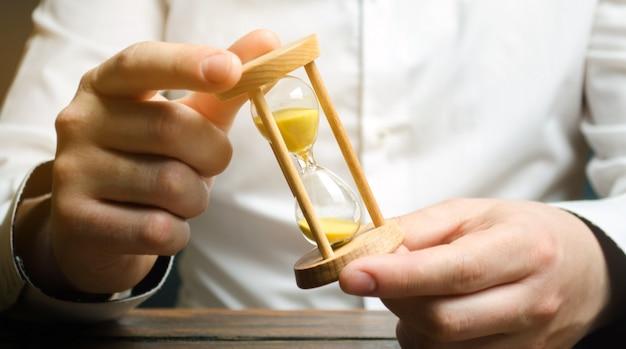 Бизнесмен держит часы в руках.
