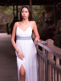 自然を離れて見ている白いドレスの美しいブルネットの少女