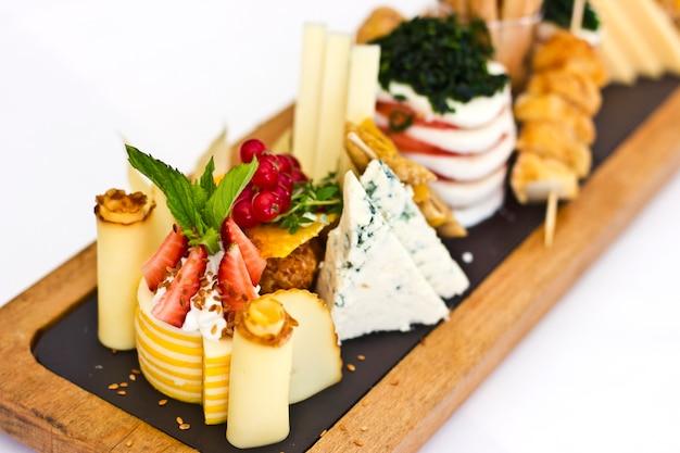 Сырная тарелка: рокфор с голубой плесенью, чеддер, копченый сыр, моцарелла на деревянной доске.