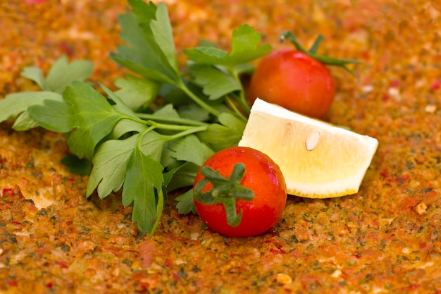 ミンチ肉とスパイスを加えたチェリートマトとパセリの葉のトルコトルティーヤピタ。