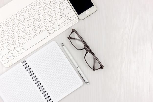 ノートパソコン、スマートフォン、眼鏡、ノートブック、コピースペースの背景を持つペンを持つ白い事務机のフラットレイアウト写真。モックアップ