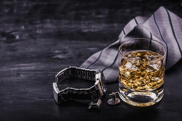 父の日の男性の概念。ネクタイ、時計、カフスボタン、氷とウィスキーのグラス