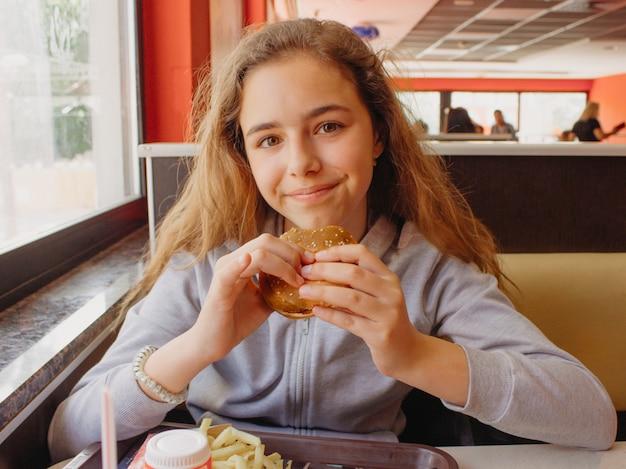 Хорошенькая молодая девушка с аппетитом ест гамбургер в кафе