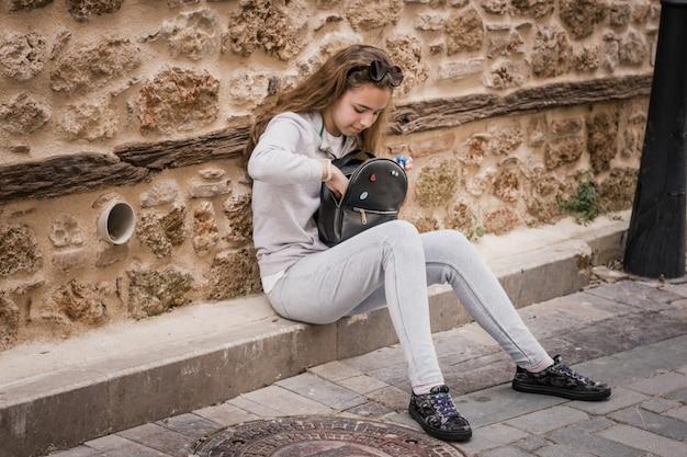 古い家の階段の上に座ってバックパックで急いで若い十代の少女