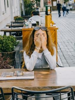 Молодая красивая девушка сидит в уличном кафе в старом городе анталии