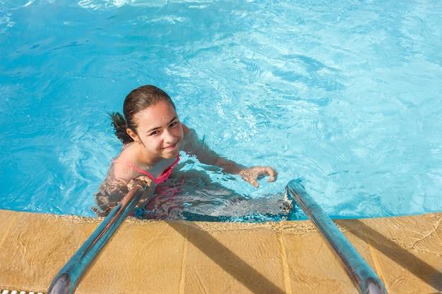 若い十代の少女が泳ぐし、屋外プールで楽しんで