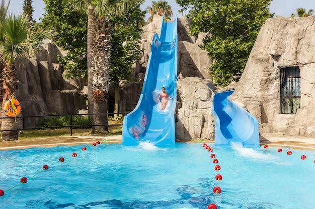 Радостная смеющаяся девушка спускается на водную горку в аквапарке отеля