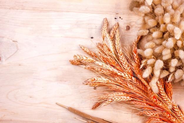 乾燥穀物の耳と葦の木製のテーブル。パンの秋の収穫