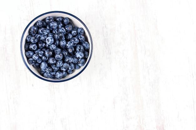 木製テーブルの上の白いボウルで新鮮なブルーベリー