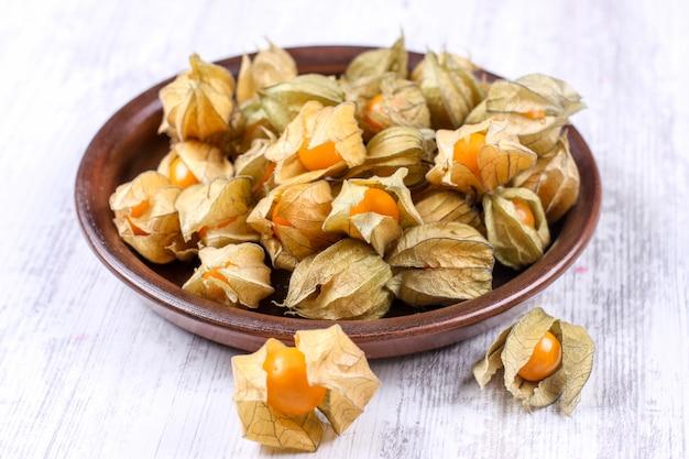 粘土皿にサイサリス。秋のホオズキ果実の熟した果実