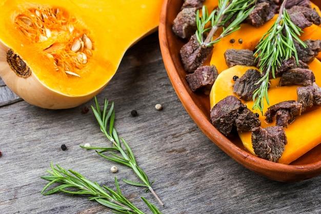 Ломтики тыквы, запеченные с мясом в глиняном горшочке. осенняя еда с розмарином и специями