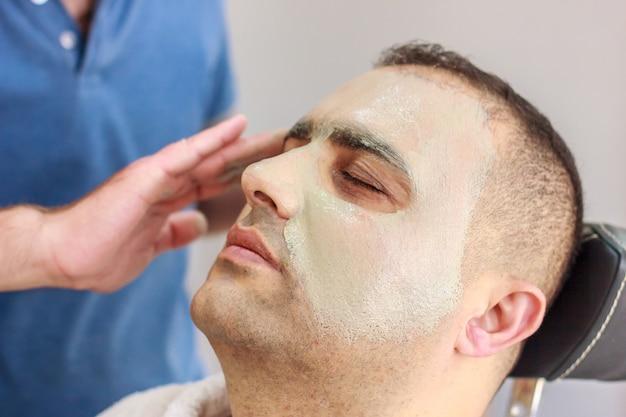 ビューティーサロンでの男性のスキンケア。男の顔にクレイクレンジングマスクを適用する