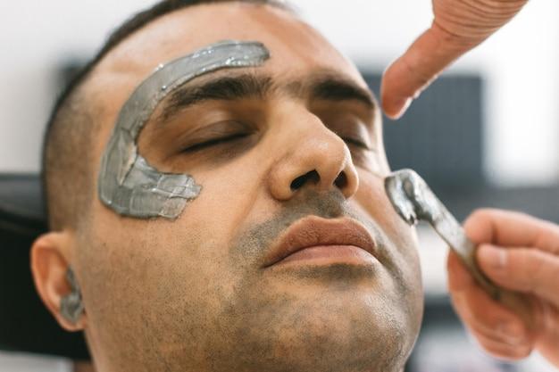 Мужское лицо воском. парикмахерская удаляет волосы, шугаринг с лица турецкого мужчины.