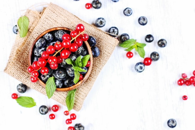Свежая черника и красная смородина с листьями мяты в деревянной миске на мешковине