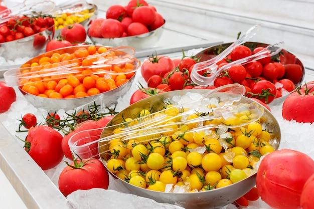 氷のボウルに黄色とピンクのトマト